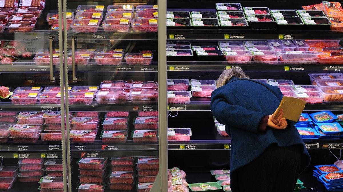 Eine Frau kauft abgepacktes Fleisch in einem Supermarkt.