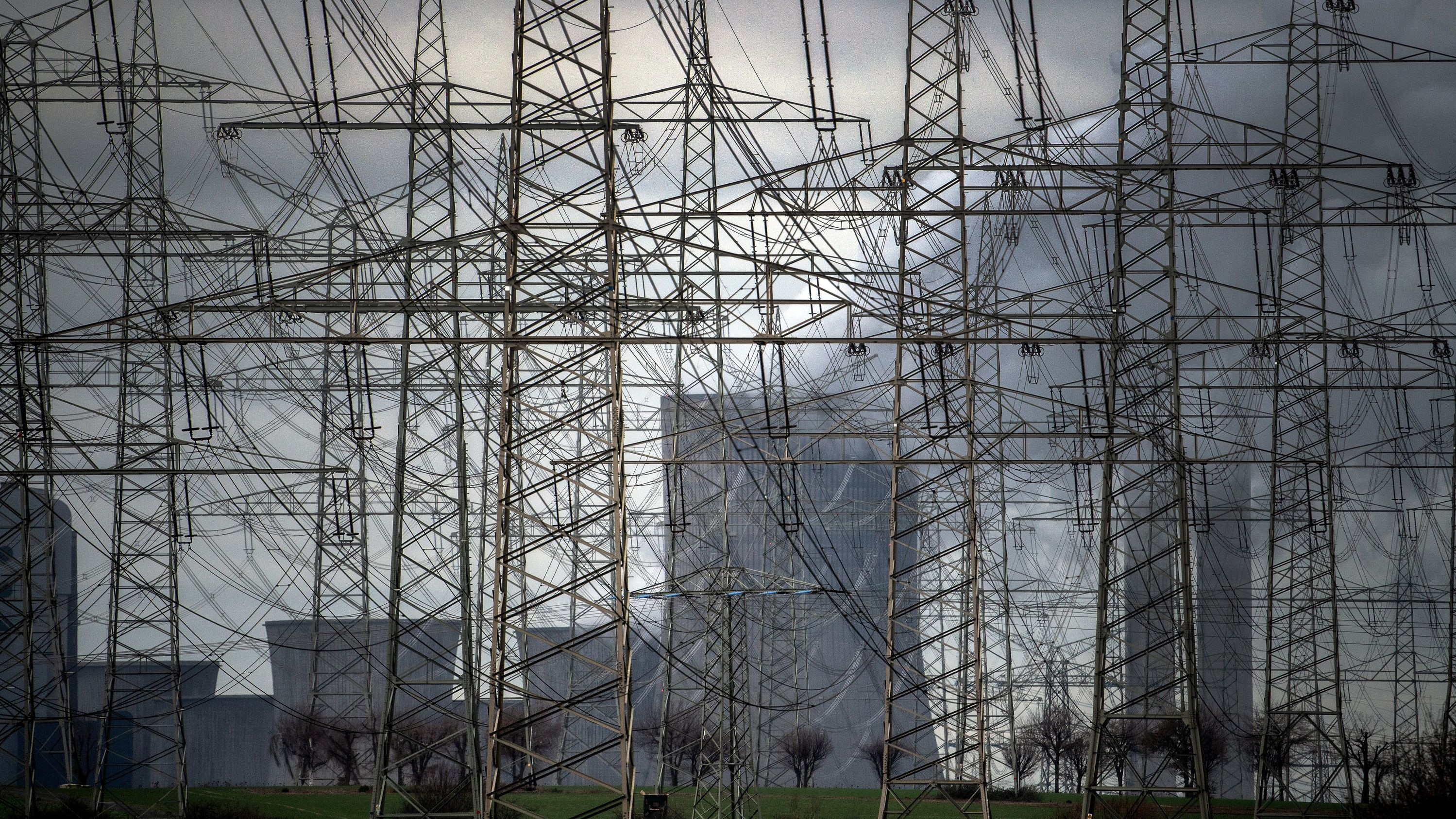 Strommasten stehen vor  einem Kraftwerk.