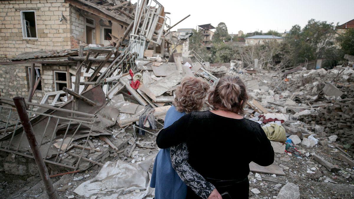 Zwei Frauen stehen Arm in Arm vor den Trümmern eines zerbombten Wohnhauses in Stepanakert