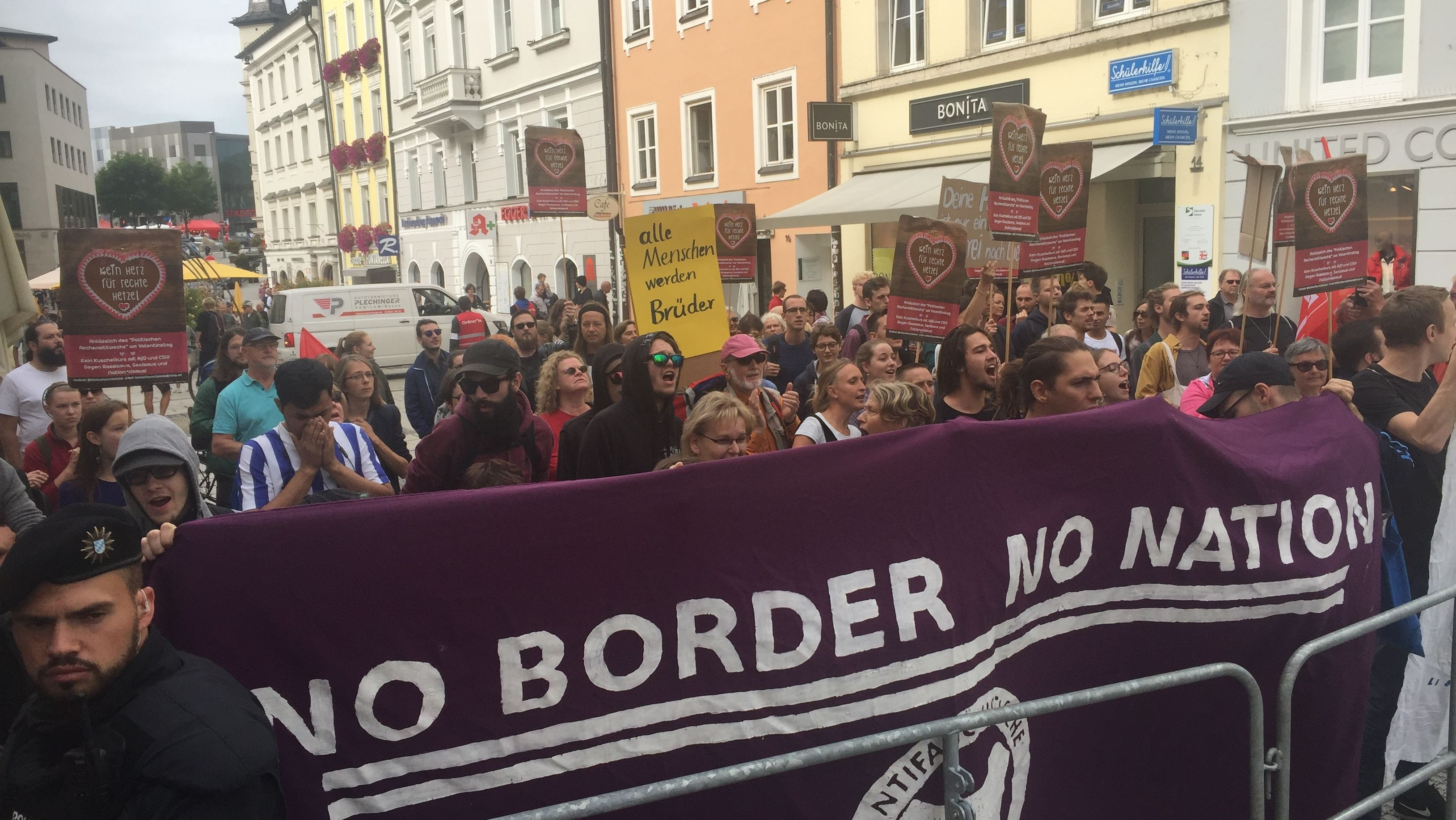 Polizist und Teilnehmer der Gegendemonstration in Passau mit Plakat