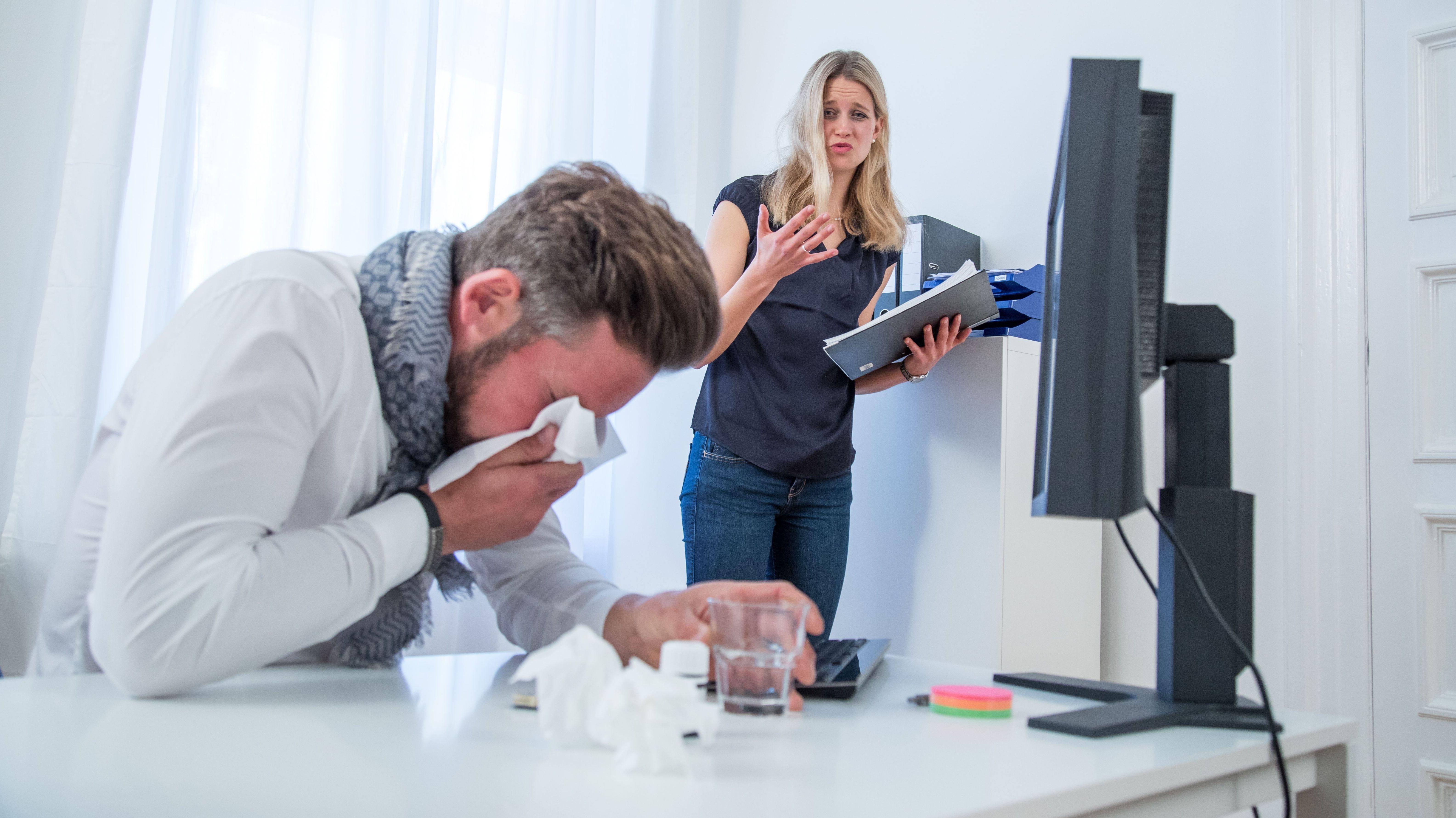 Ein Mann mit Erkältung im Büro