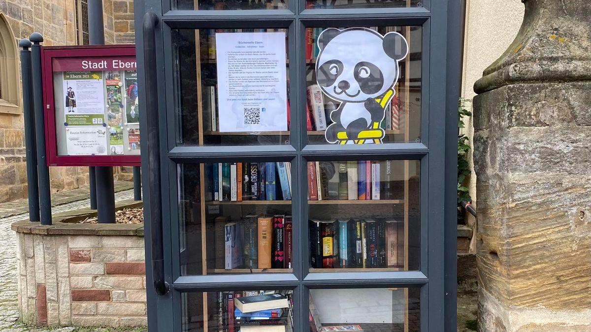 Auch in einer ehemaligen Telefonzelle, die jetzt eine Bücherbox ist, hängt ein Pandabär.