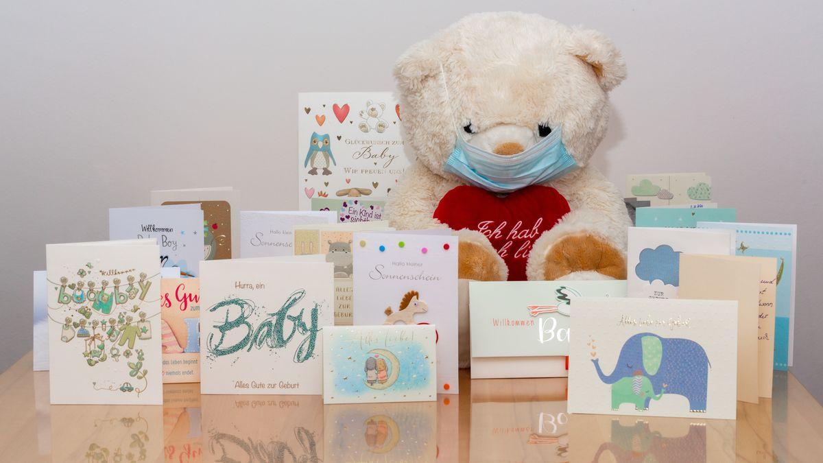 Teddybär mit Mund-Nasen-Schutz und Glückwunschkarten zur Geburt
