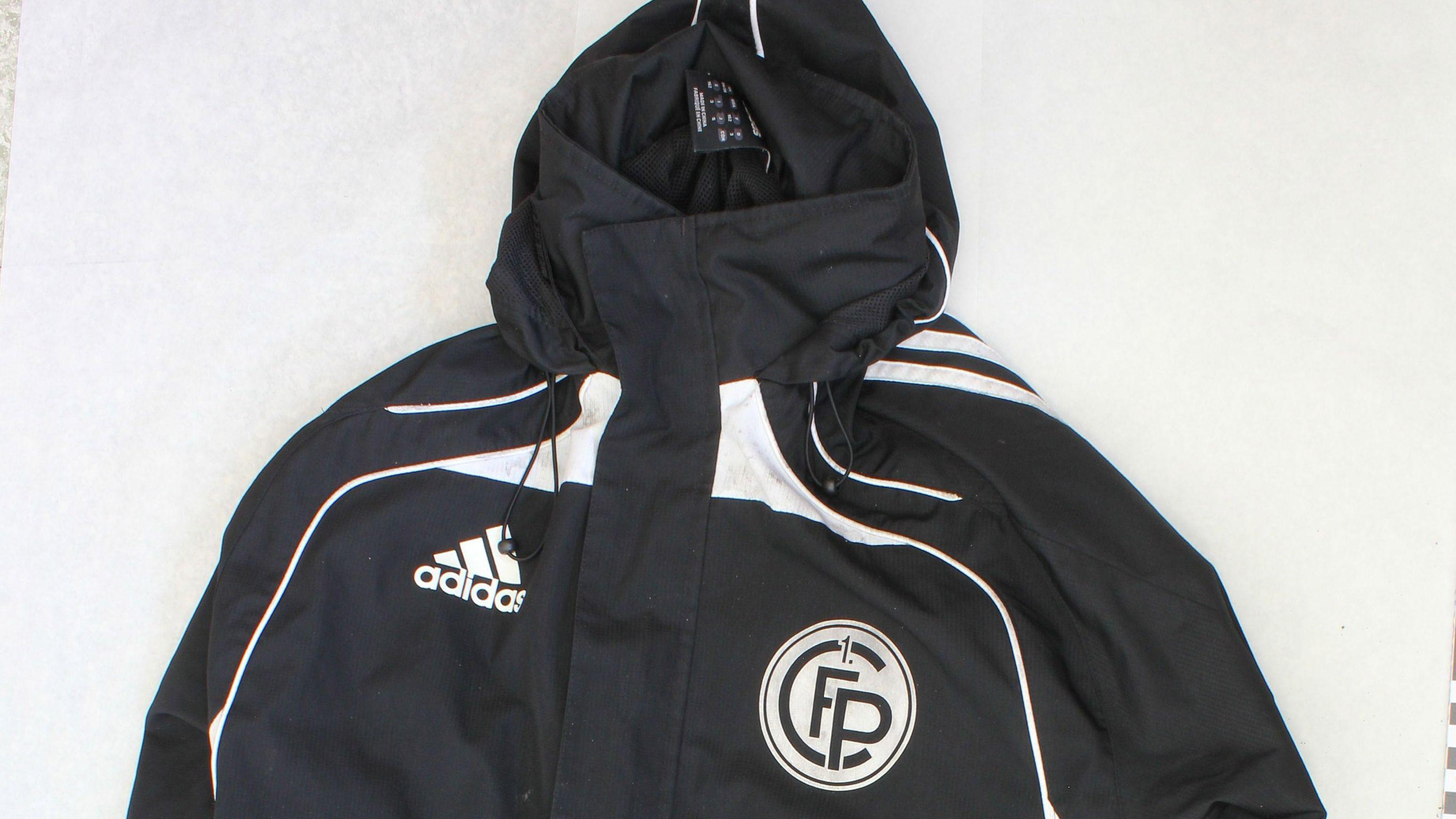 """Der Unbekannte trug eine schwarze Sport-/Trainingsjacke der Marke """"adidas"""", das Logo des 1. FC Passau ist darauf abgebildet."""