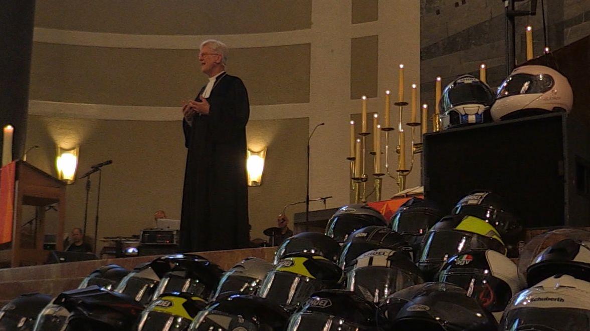 Der EKD-Ratsvorsitzende beim Biker-Gottesdienst neben zum Gebet abgenommenen Motorrad-Helmen.