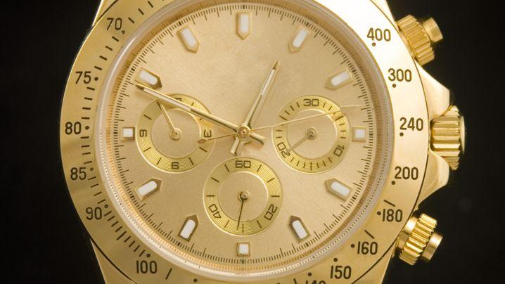 Luxuriöse goldene Uhr auf schwarzen Hintergrund.