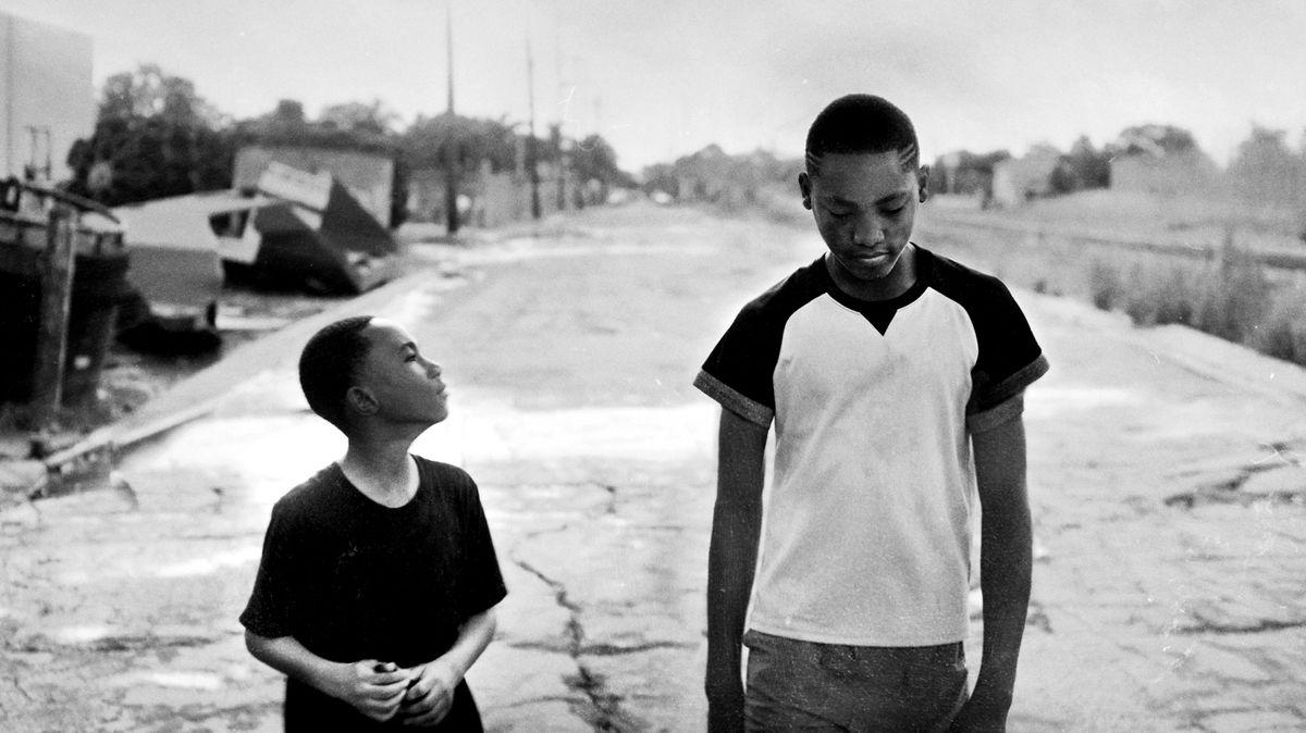 2 schwarze Jungs mit kurzen Haaren gehen über eine aufgerissene Straße in einer trostlosen Gegend