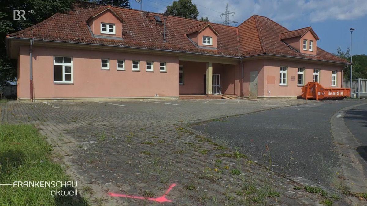 Zu sehen ist ein rosa getünchtes Gebäude mit einem Satteldach.