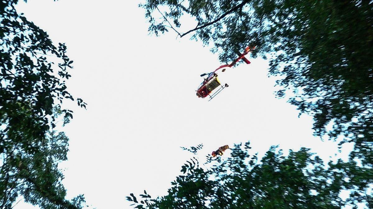 Ein Hubschrauber über einem Wald. An ihm hängt an einer Seilwinde ein Schwerverletzter, dazu ein Retter der Bergwacht.