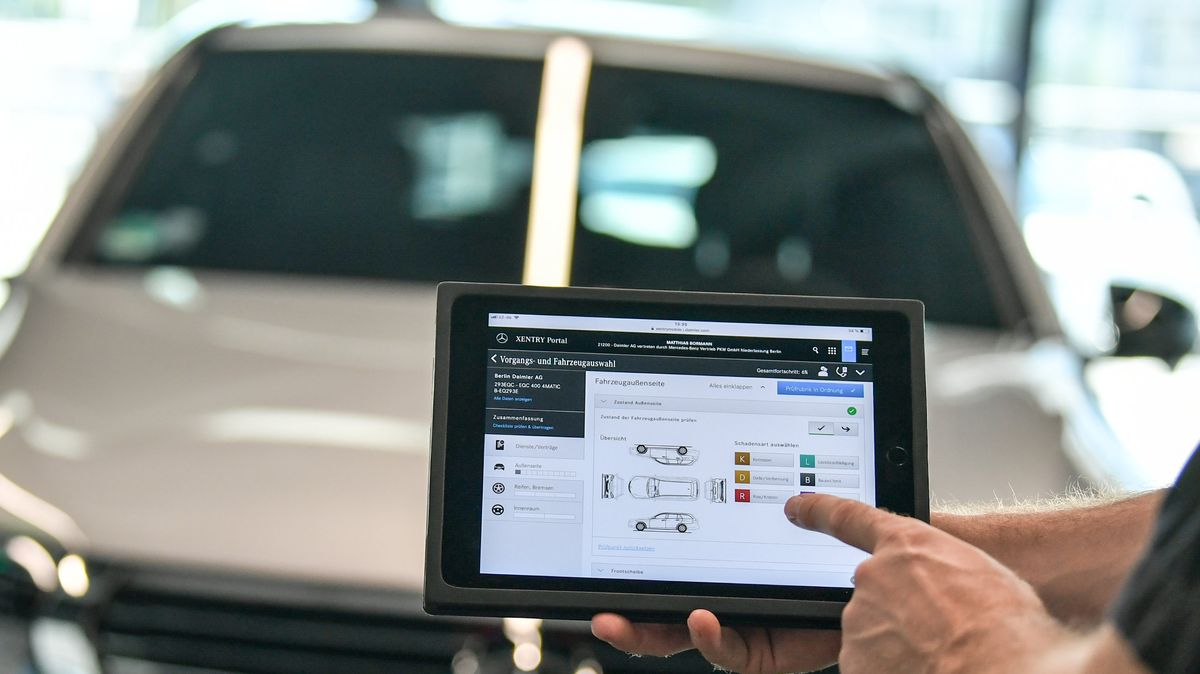 Ein Tablet vor einem Auto in einer Werkstatt zeigt die Möglichkeiten der Digitalisierung.