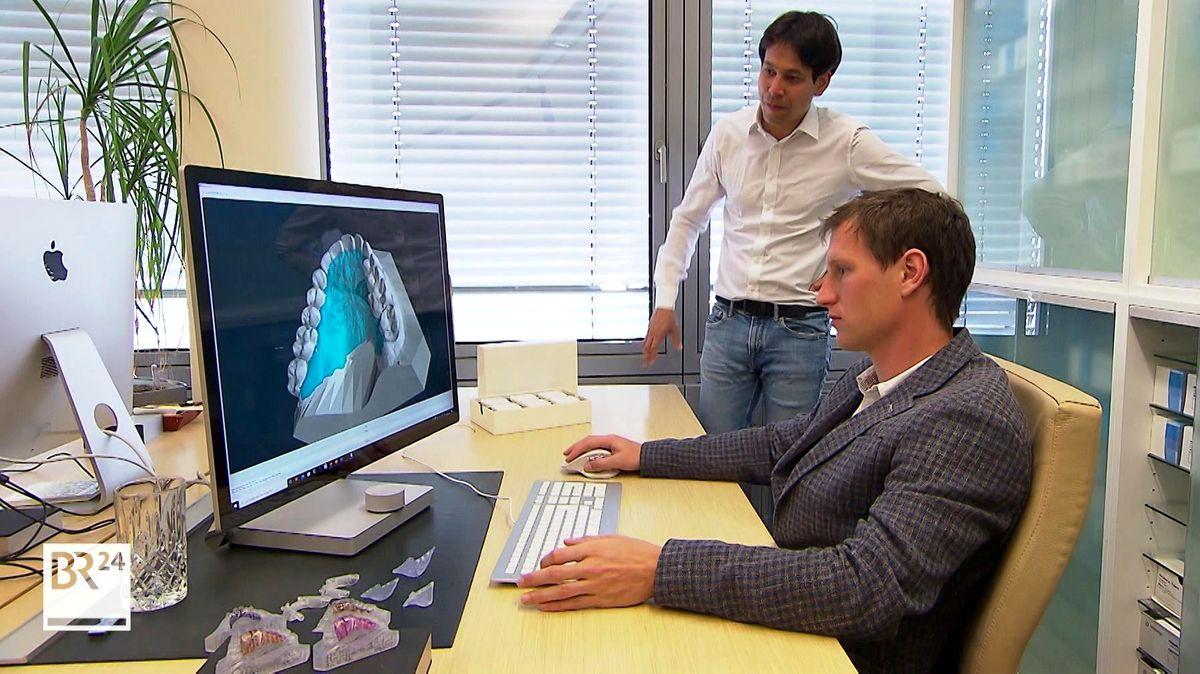Zwei Männer betrachten eine dreidimensionale Darstellung eines Kiefers auf einem PC-Bildschirm.