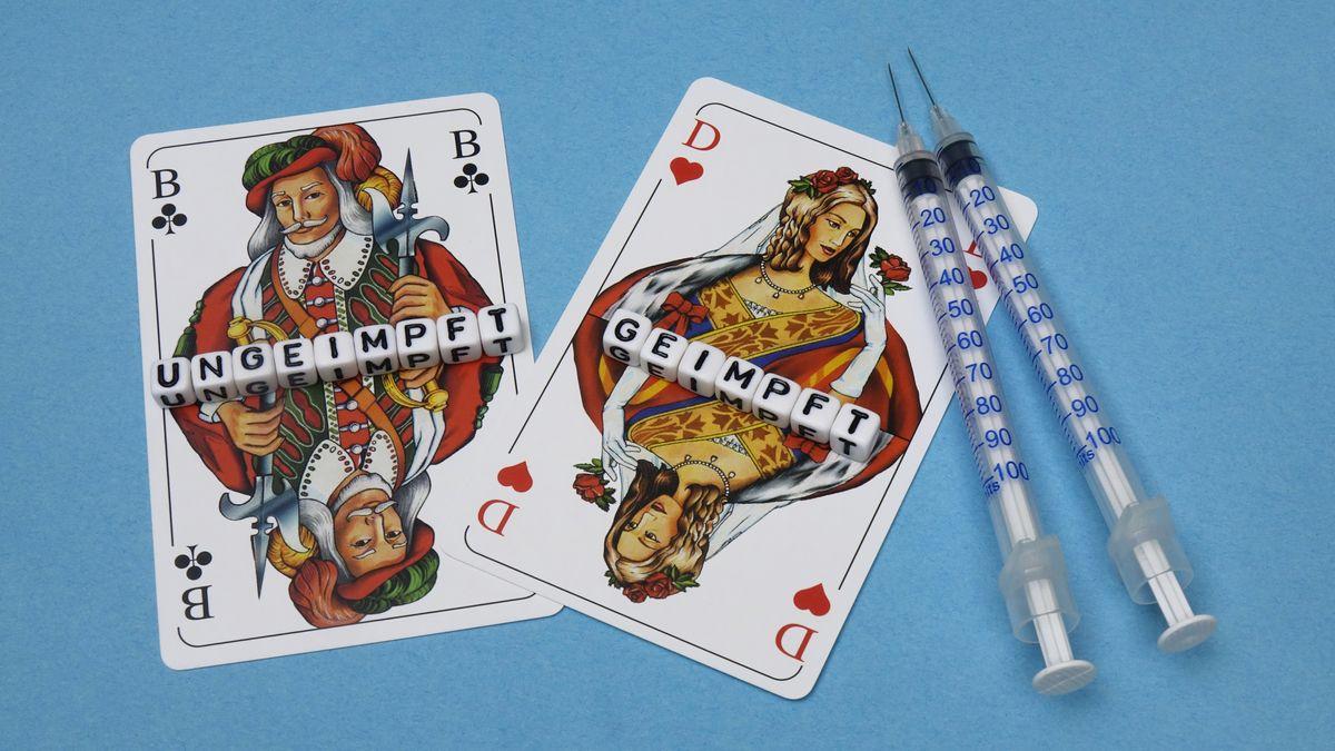 Auf zwei Spielkarten liegen die Schriftzüge geimpft und ungeimpft.