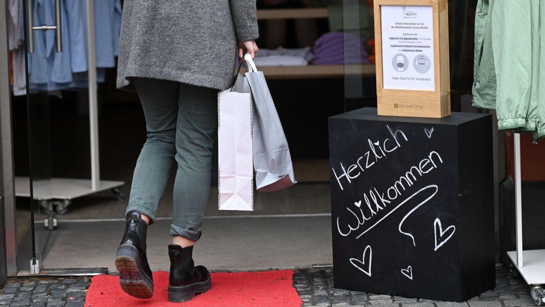 Eine Frau mit Einkaufstaschen betritt ein Modegeschäft