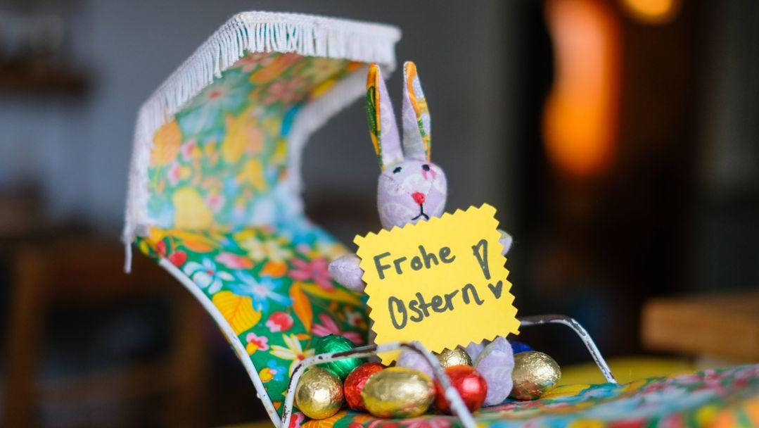 Ein Hase sitzt mit bunten Ostereiern im Liegestuhl