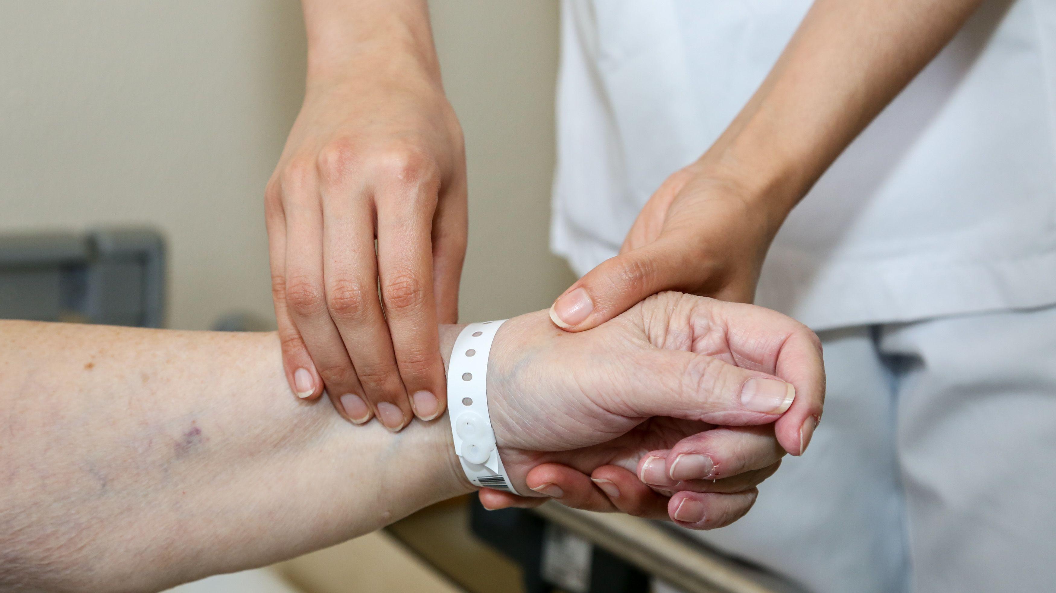 Krankenpflegeschülerin tastet den Puls einer Patientin