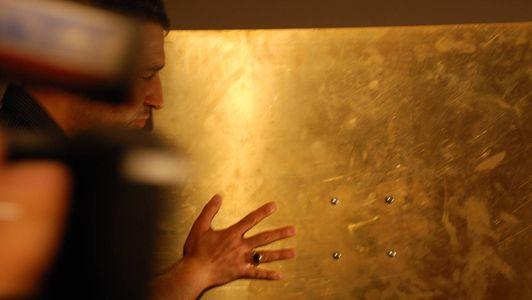 Ein Mann hält seine rechte Hand auf eine Metallwand und fühlt konzentriert