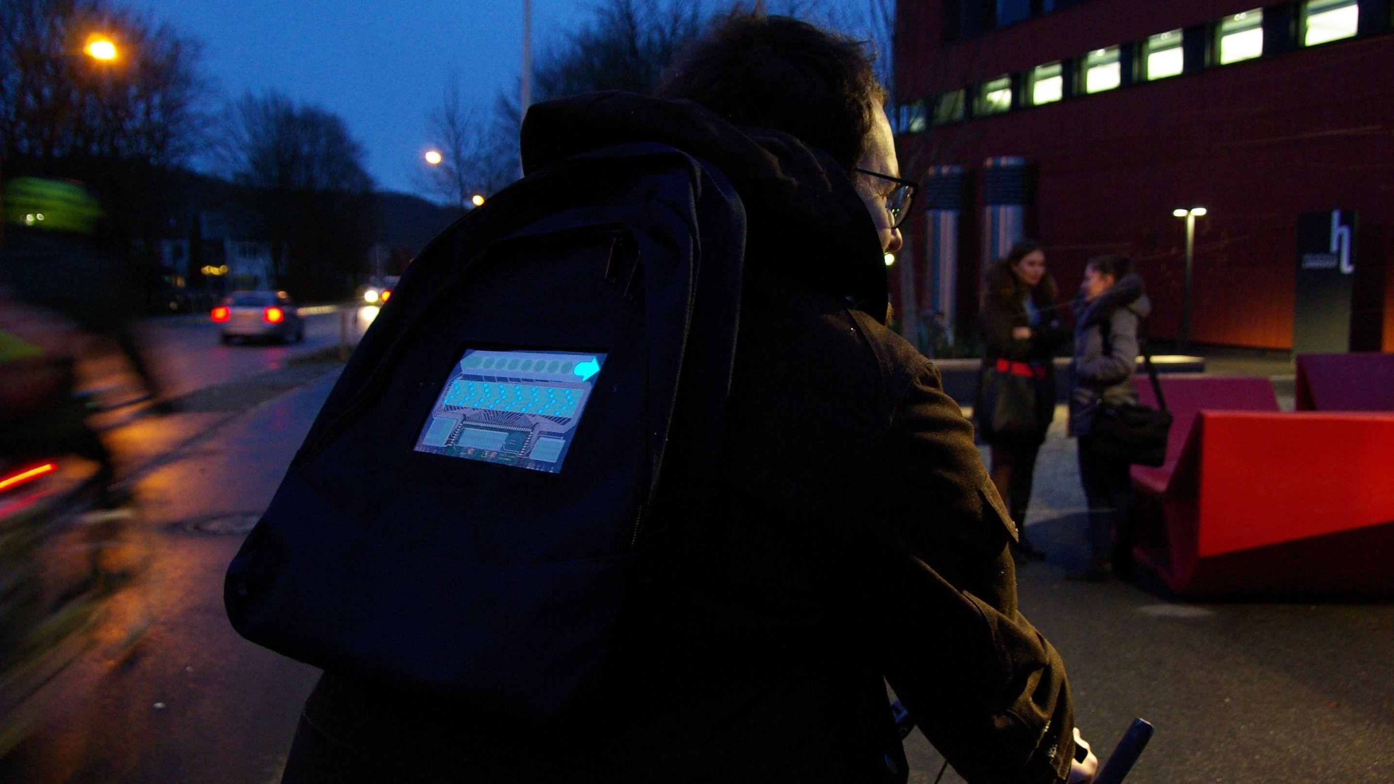 Ein Fahrradfahrer trägt in der Dunkelheit eine Blinker-Jacke