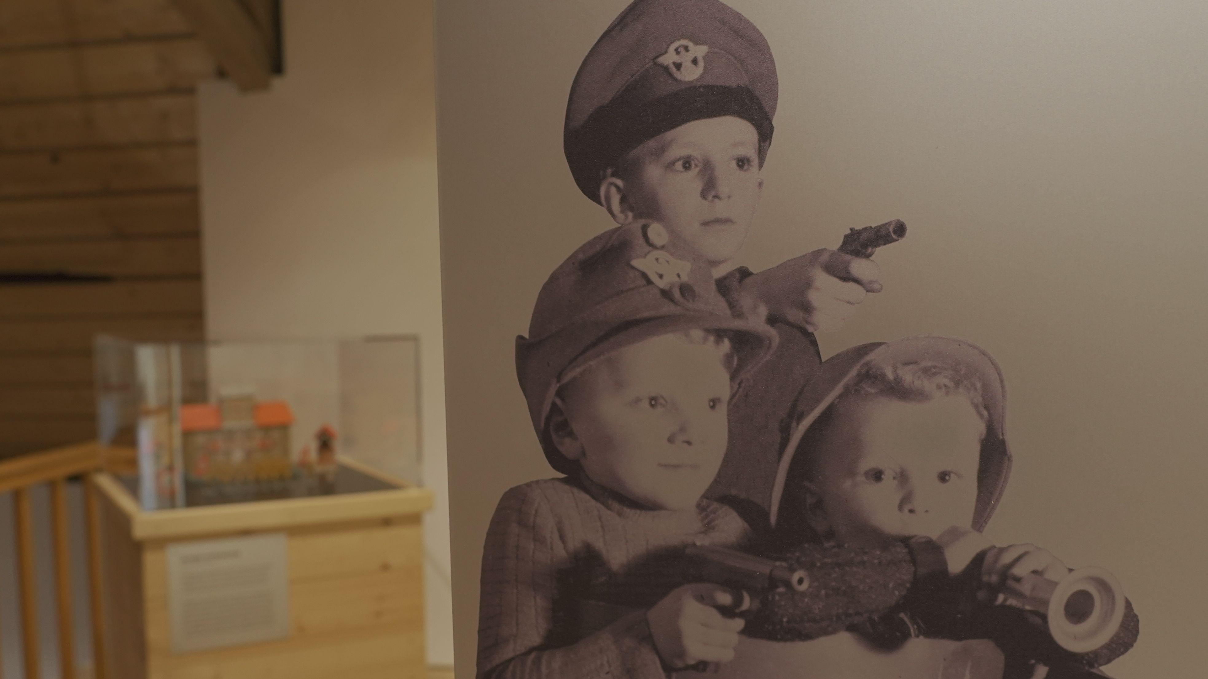 Altes Bild mit Kinder mit Spielzeugwaffen und Uniformen.