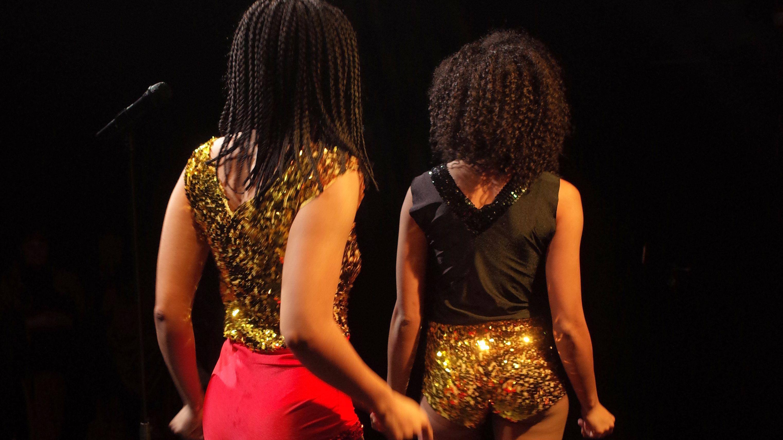 Zwei arfodeutsche Frauen tanzen auf der Bühne in glitzernder Bekleidung