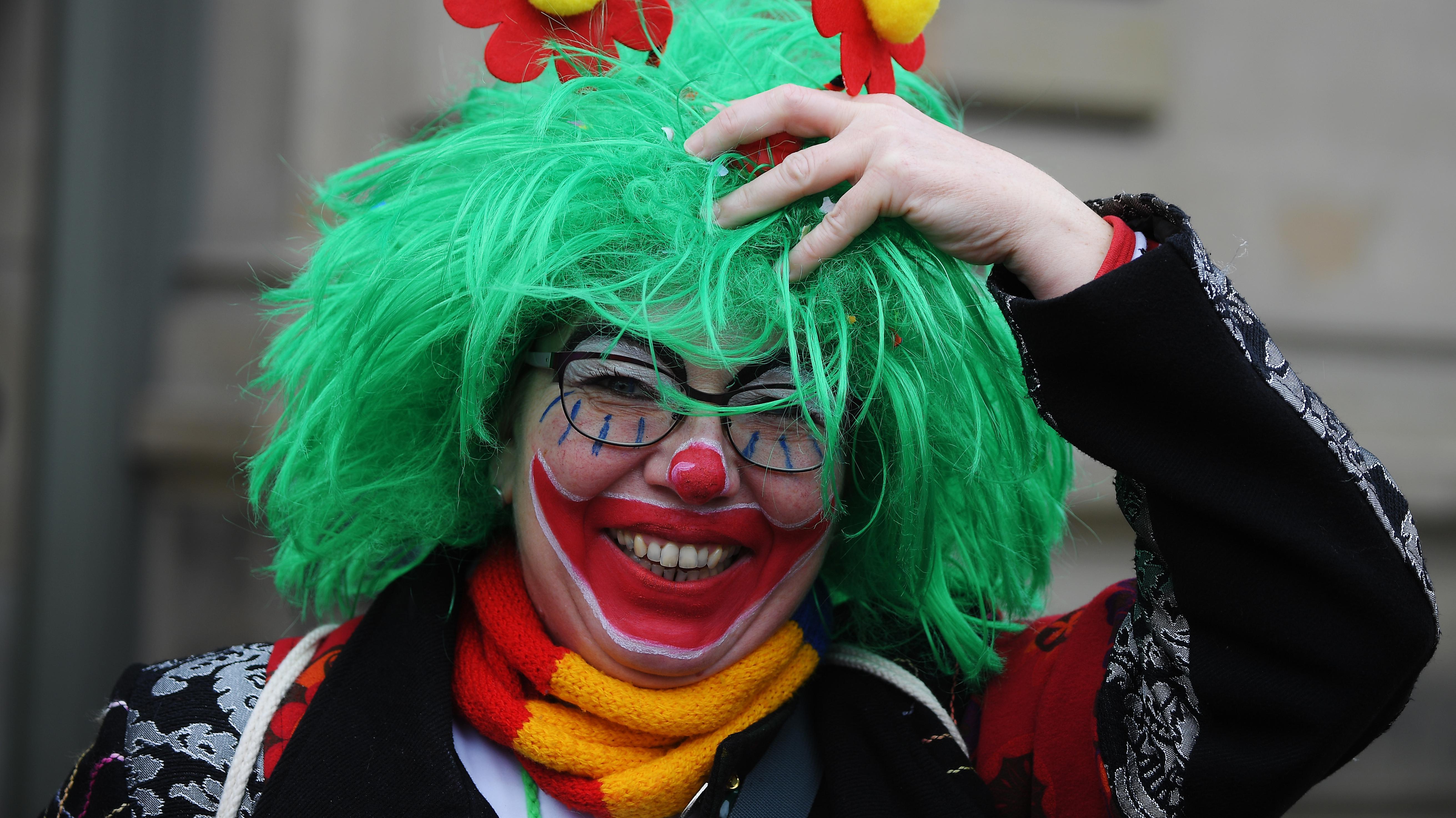 Eine Zuschauerin des Mainzer Rosenmontagszuges hält sich in einer Windböe die Perücke fest