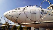 Hinter einem Stacheldrahtzaun steht eine Flugzeug auf dem Rollfeld.  | Bild:picture alliance/Geisler-Fotopress
