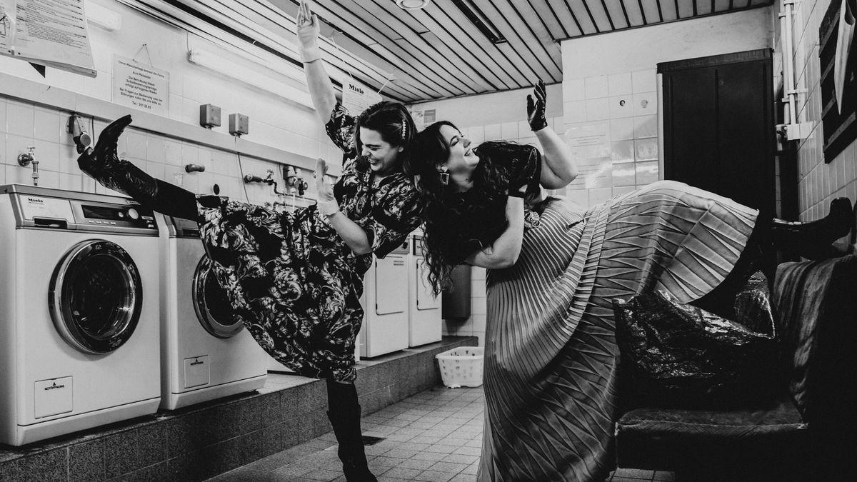 Zwei Frauen in Kleidern tanzen im Waschkeller.