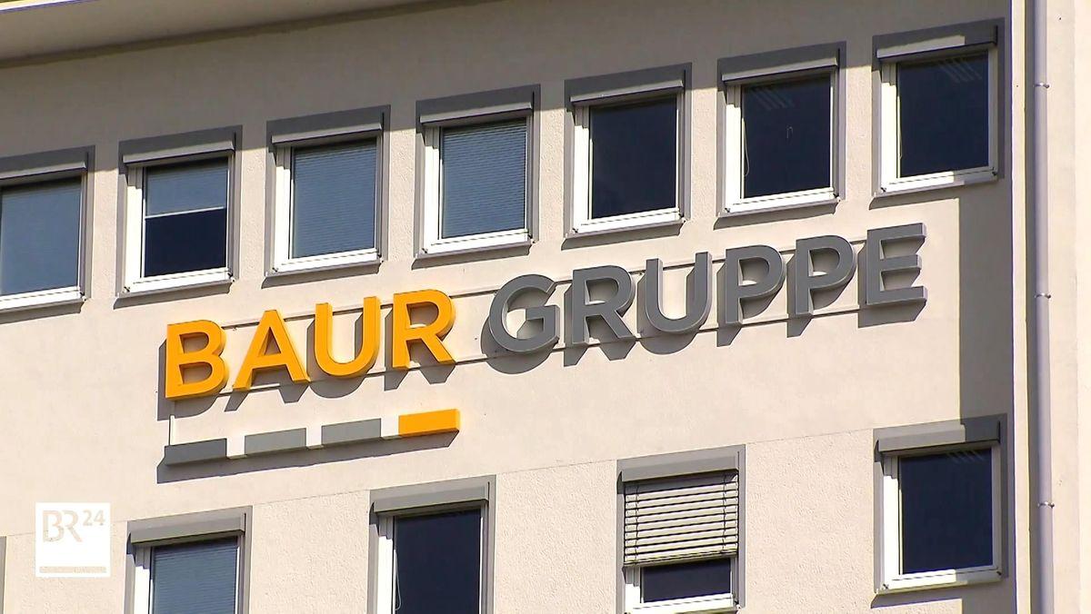 """Auf der Fassade eines Gebäudes steht in gelben und grauer Schrift """"Baur Gruppe"""""""