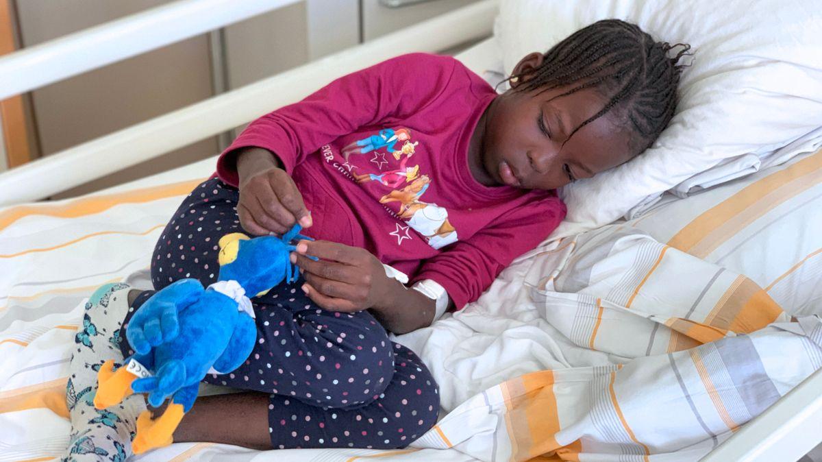 Isatou liegt auf einem Bett im Kinderkrankenhaus St. Hedwig in Regensburg.