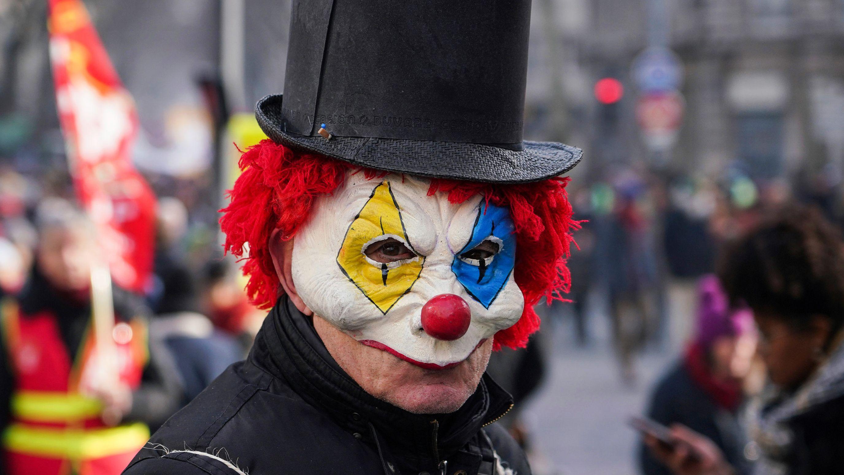 Frankreich, Lyon: Ein Demonstrant trägt am 24.1.2020 während eines Protestes gegen die geplanten Rentenreformen eine Clownsmaske und einen Zylinder.