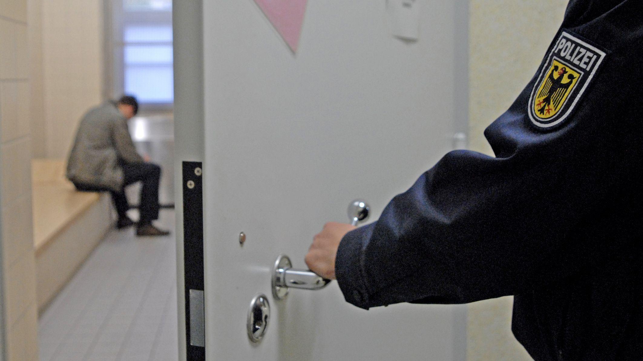 Mann sitzt in Gewahrsam, ein Polizist öffnet die Tür. (Symbolbild)