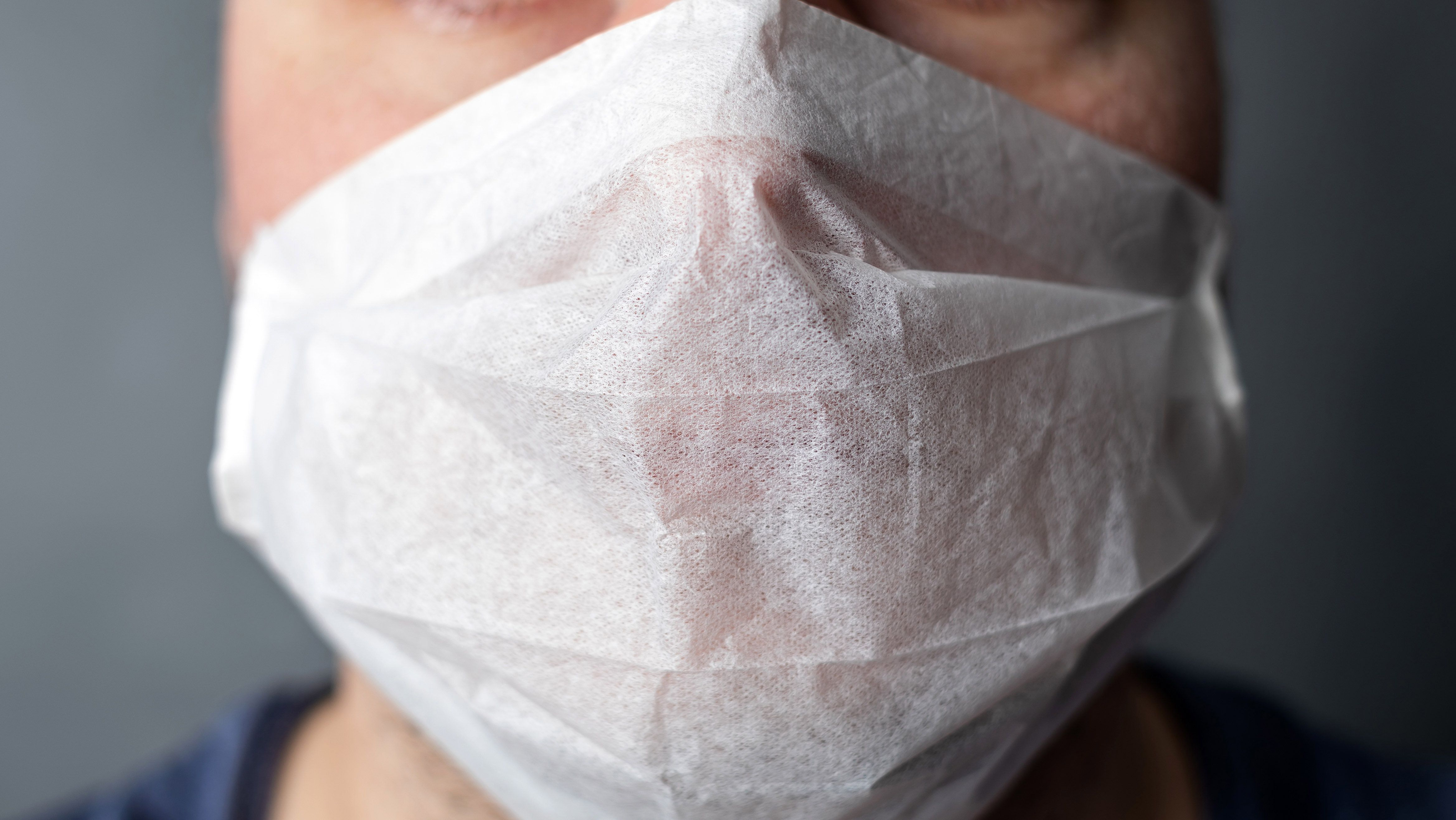 Mensch mit Atemschutzmaske in einer Deatilaufnahme (Symbolbild).