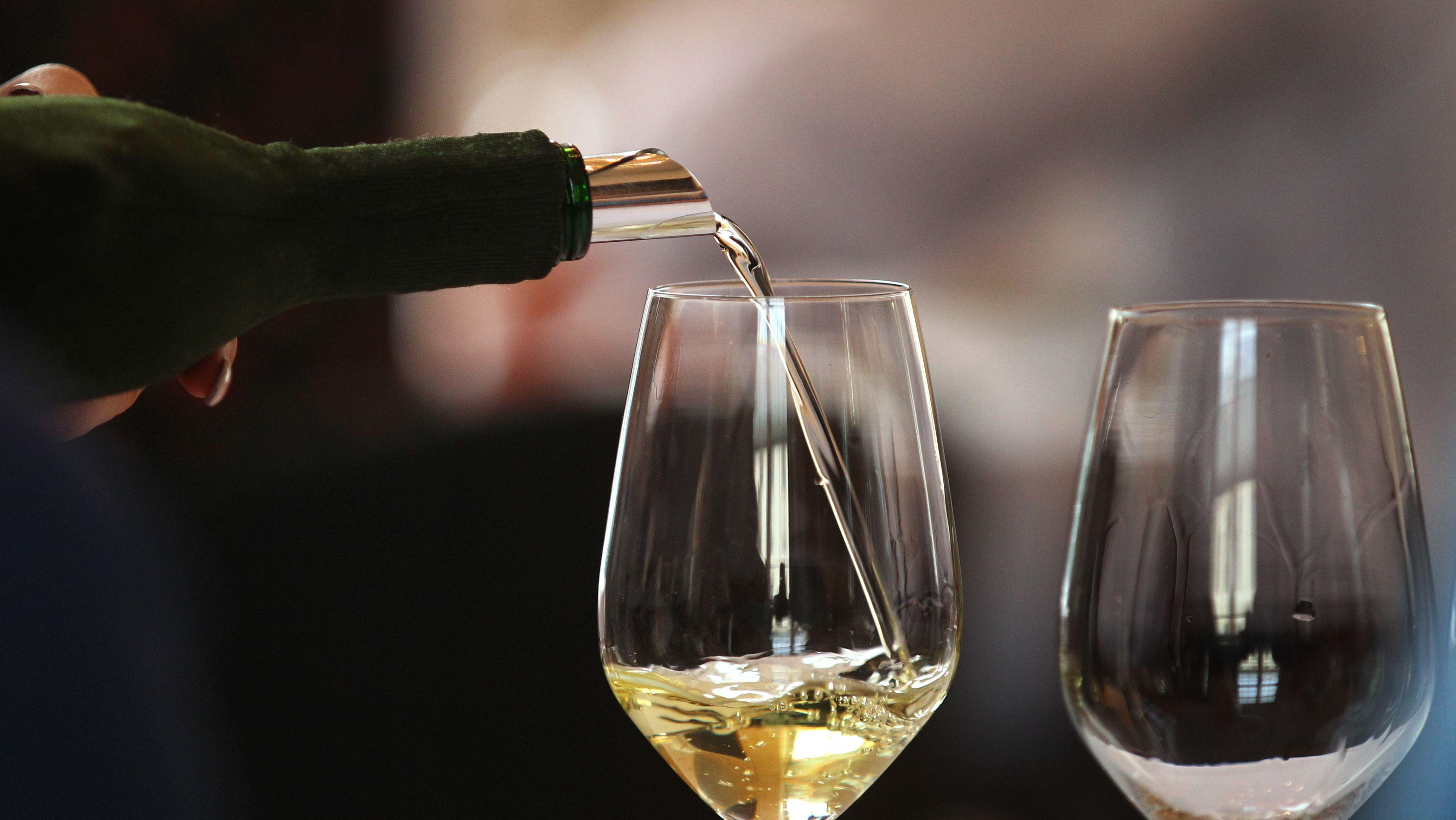 Weinglas wird mit Weißwein gefüllt.
