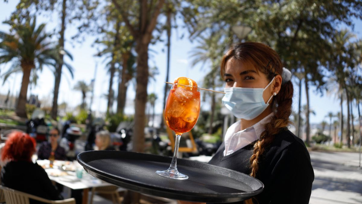 Kellnerin auf Mallorca trägt einen Cocktail auf dem Tablett.