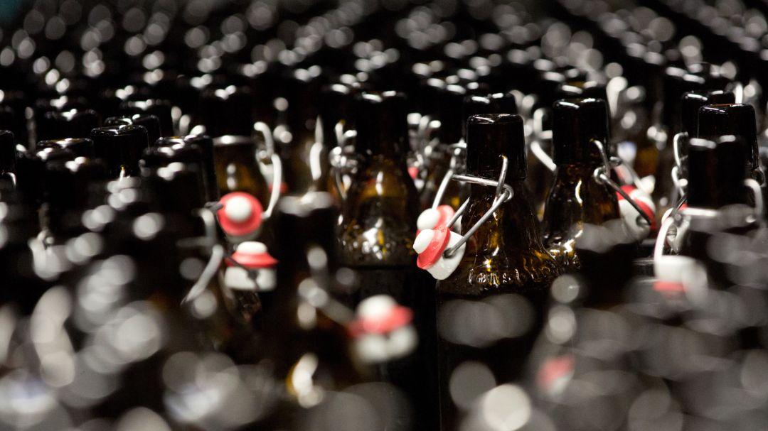 Bierflaschen laufen in der Abfüllhalle einer Brauerei zur Abfüllstation.